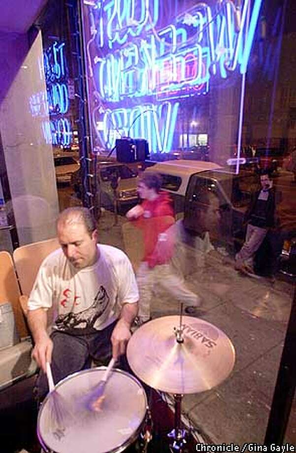 Jimmy Monack, the drummer with Small Wonder, plays in the window of Lost Weekend Video, which features bands in the store on weekend evenings. Chronicle photo by Gina Gayle