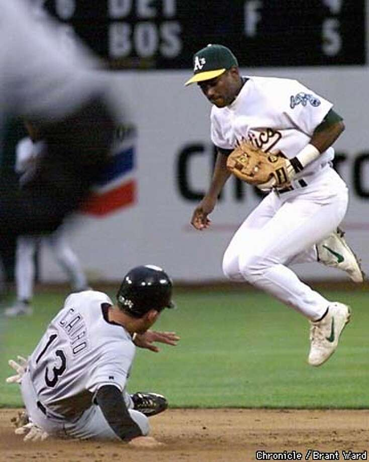 A'S-2ND/01JUN99/SP/BW--Miguel Cairo slid hard into second base to break up a double play in the 2nd inning. Miguel Tejada defends. By Brant Ward/Chronicle Photo: BRANT WARD