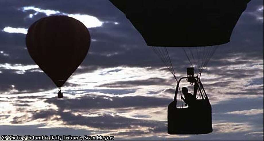 """David Levin, piloting his Boulder, Colo., balloon """"Red Dog III"""", prepares to throw a beanbag streamer at a designated target early Thursday, Aug. 14, 1997 in Columbia, Mo. Pilots were competing for points during the U.S. National Hot Air Balloon Championships which began Aug. 8, 1997. Levin is currently in second place. (AP Photo/Columbia Daily Tribune, Sean Meyers) Photo: SEAN MEYERS"""
