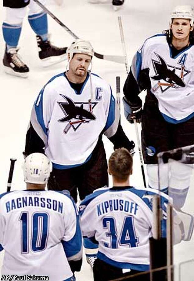 San Jose Sharks' Owen Nolan, upper left, and Mike Ricci, right, skate toward Marcus Ragnarsson, lower left, and Miikka Kiprusoff, lower right, after the Blues defeated the San Jose Sharks 2-1 in their first round playoff series in San Jose, Calif., Saturday, April 21, 2001. The Blues won the series 4-2 to advance to the next round. (AP Photo/Paul Sakuma) Photo: PAUL SAKUMA