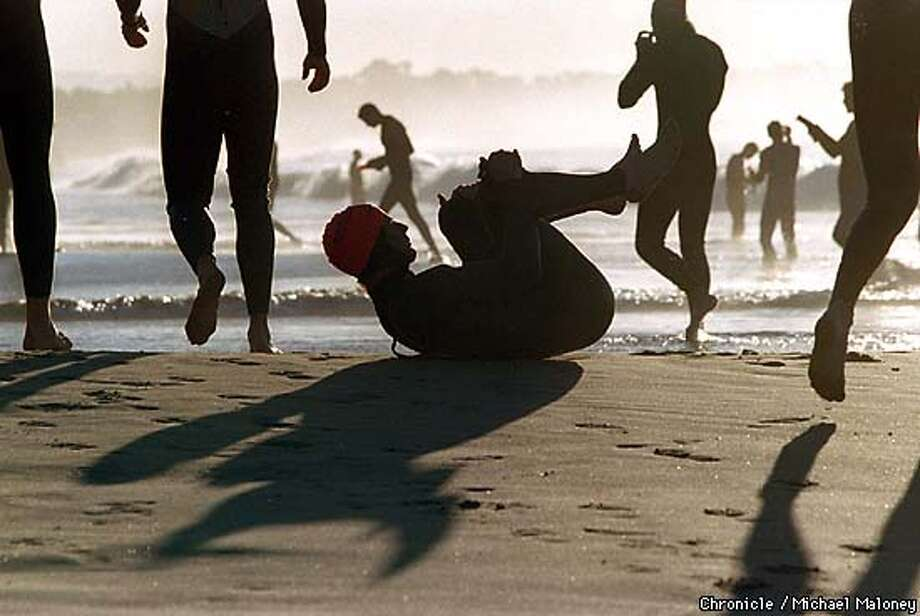 Triathletes stretch and prepare for the Santa Cruz Triathlon.  Photo by Michael Maloney  JUDGES COMMENTS: We all liked the energy in this great photo by Mike Maloney. You can feel the adrenaline pumping in these athletes waiting to compete in the Santa Cruz Triathlon. Photo: MICHAEL MALONEY