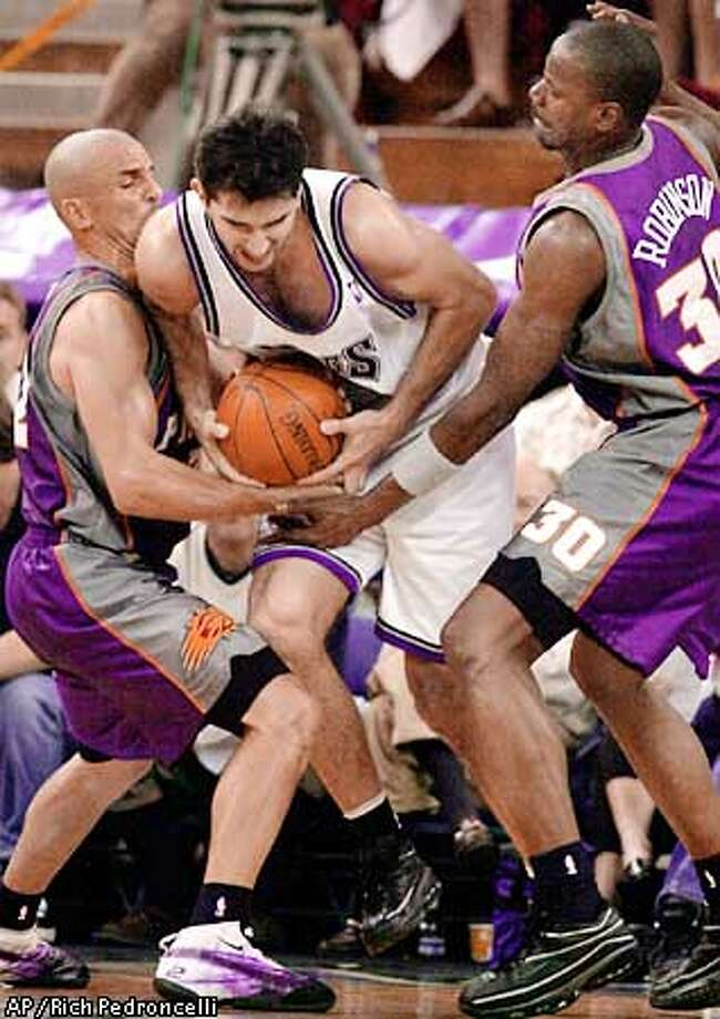 Sacramento Kings forward Predrag Stojakovic, center, is double-teamed and trapped by Phoenix Suns' Jason Kidd, left, and Cliff Robinson during the fourth quarter of their first round playoff game played at Arco Arena in Sacramento, Calif., Sunday, April 22, 2001. The Suns went on to defeat the Kings 86-83 to take a 1-0 lead in the series.(AP Photo/Rich Pedroncelli) Photo: RICH PEDRONCELLI