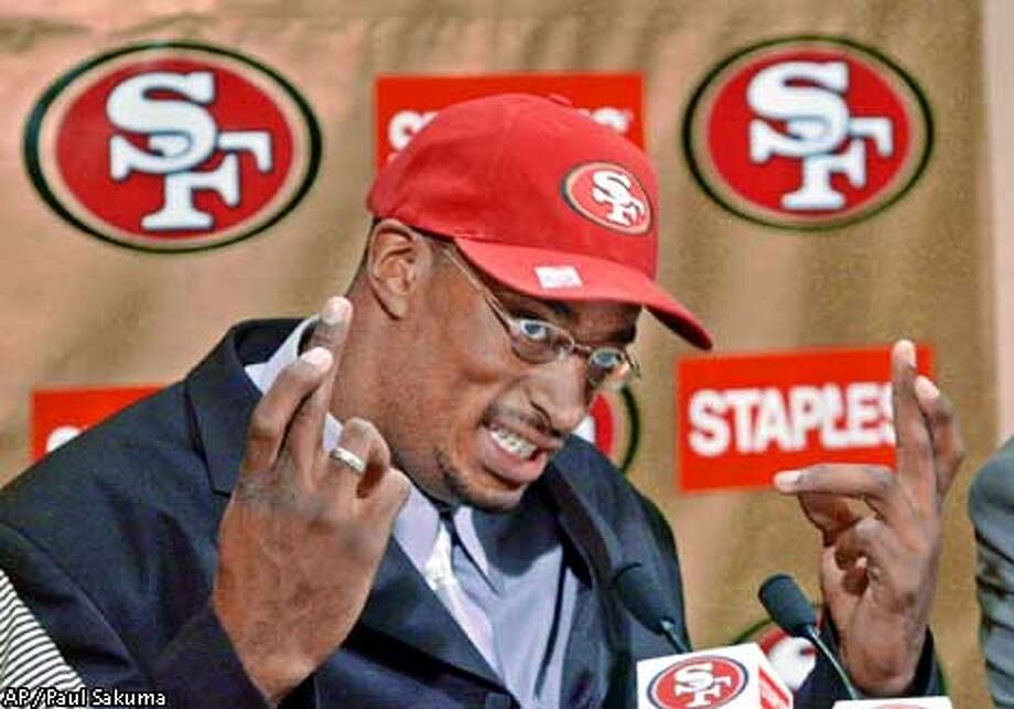 San Francisco 49ers first-round draft pick Andre Carter crosses his fingers during a news conference at 49ers headquarters in Santa Clara, Calif., Sunday, April 22, 2001, as he talks about how he hoped to be drafted by the 49ers. Carter, a defensive end at California, is the son of former Denver Broncos nose tackle and current New York Jets defensive line coach Rubin Carter. (AP Photo/Paul Sakuma) Photo: PAUL SAKUMA