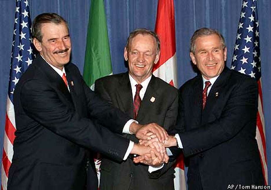 Mexican President Vicente Fox, Canadian Prime Minister Jean Chretien and U.S. President George W. Bush clasp their hands together after a meeting between the three leaders after the closing of the Summit of the Americas in Quebec City, April 22, 2001. Western Hemisphere leaders signed an agreement Sunday to open their markets by December 2005, and said only countries with democratic governments can be a part of the world's most ambitious free-trade zone. (AP Photo/Canadian Press, Tom Hanson) Photo: TOM HANSON