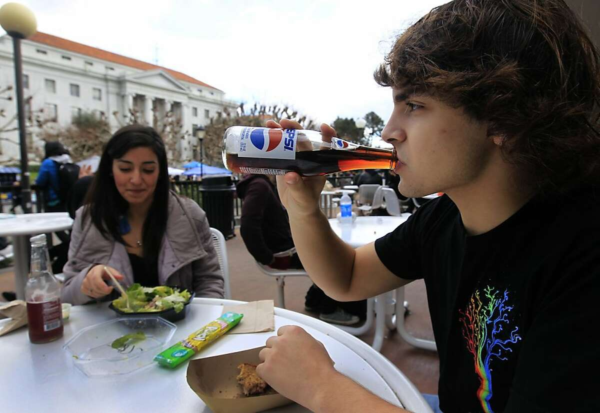 Freshman Sam Friedman consumes a soft drink while having lunch with Amare Silva on Sproul Plaza at UC Berkeley on Wednesday, Feb. 1, 2012. An article by UCSF scientists suggests that sugar is a controlled substance that should be subjected to government regulations.