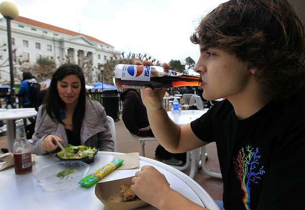 Freshman Sam Friedman consumes a soft drink while having lunch with Amare Silva on Sproul Plaza at UC Berkeley on Wednesday, Feb. 1, 2012. An article by UCSF scientists suggests that sugar is a controlled substance that should be subjected to government regulations. Photo: Paul Chinn, The Chronicle