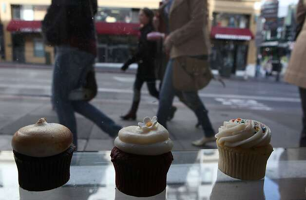 Cupcakes lined up at Cako bakery in San Francisco, Calif., as pedestrians pass by on Wednesday, February 1, 2012. Three UCSF scientists are saying sugar is a significant public danger. Photo: Liz Hafalia, The Chronicle