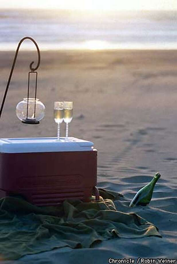 By the Sea picnic features two glasses of sparkling wine on top of a cooler, a blanket and a lantern at Ocean Beach in San Francisco.  BY ROBIN WEINER/THE CHRONICLE Photo: ROBIN WEINER