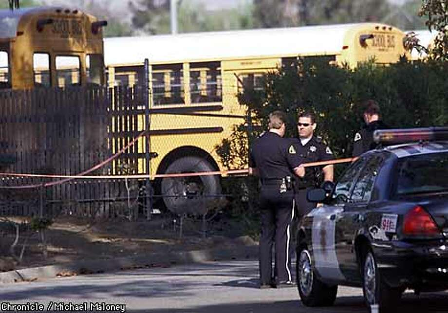 San Jose police officers guard the entrance to the Laidlaw school bus yard.  One man was killed, three women injured early this morningin a shooting rampage at a Laidlaw school bus yard on Remillard Court in San Jose. The gunman, a female bus driver was arrested at the scene. All the victims were employees of Laidlaw.  CHRONICLE PHOTO BY MICHAEL MALONEY Photo: MICHAEL MALONEY