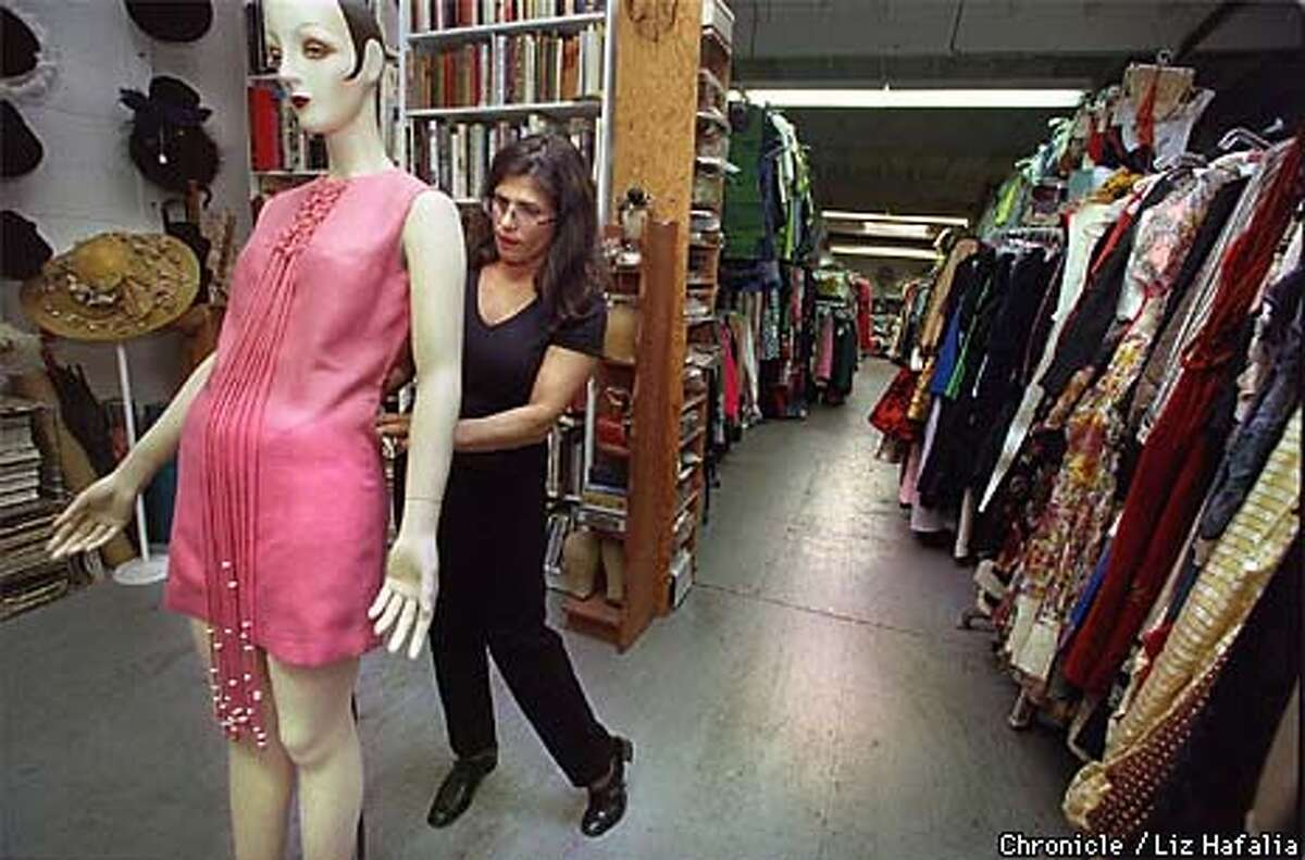 """Doris Raymond places a 1971 pink linen dress worn by Kathleen Quinlan in """"Apollo 13"""". Raymond has a collection of close to 100,000 vintage garments. She rents these clothes to Hollywood studios for films and tv shows. BY LIZ HAFALIA/THE CHRONICLE"""