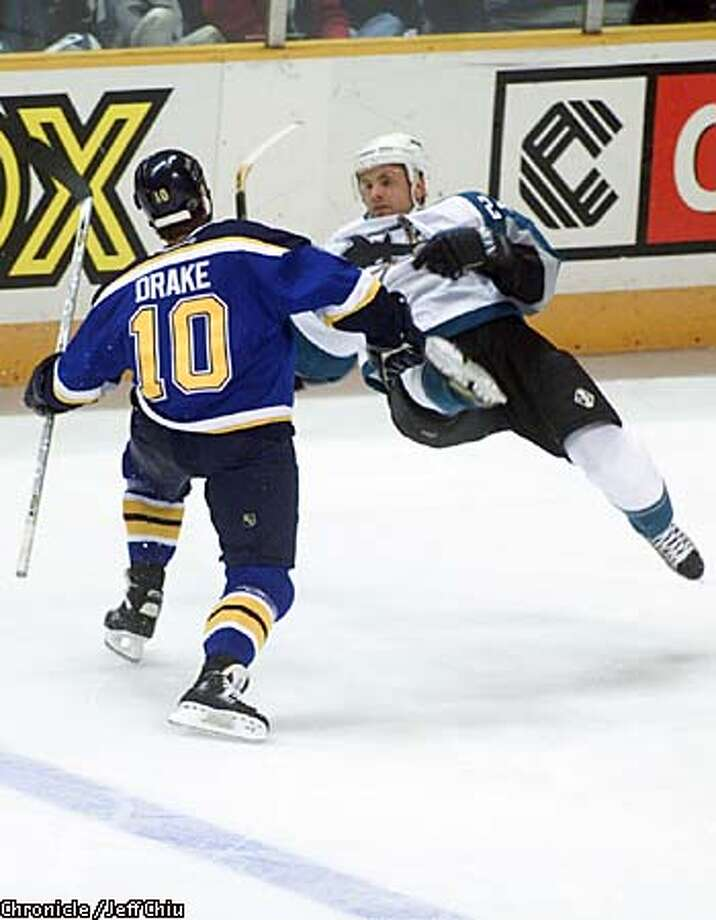 Niklas Sundstrom of the Sharks is leveled by the Blues' Dallas Drake in the first period. Chronicle photo by Jeff Chiu