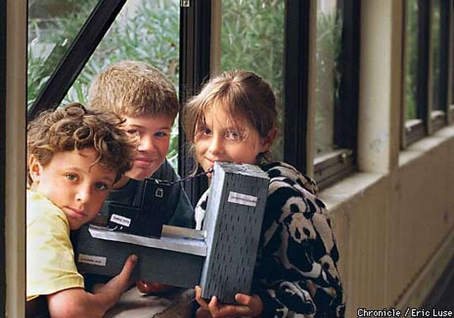 Alejo Kraus Polk,9, Nico Martinucci,9, and Emma Cox,9, all from Jefferson School, Berkeley hold a model they build to help explaing why the school's windows still leak. They discovered the lack of flashing is contributing to the leak.  BY ERIC LUSE/THE CHRONICLE Photo: ERIC LUSE