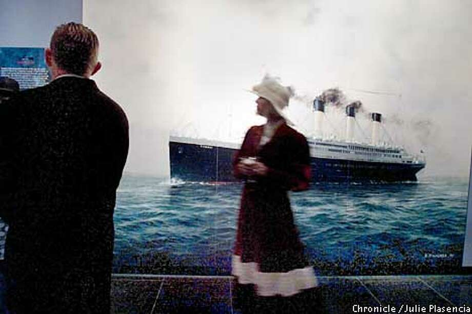 """Dressed in the typical adornments of the early 1900's Sally Beaudry glances at a rendering of the Royal Mail Steamer Titanic at the entrance of the exhibition """"Posted Aboard RMS Titanic"""" at the Blackhawk museum in Danville during a museum fundraiser and the exhibits grand opening.  (JULIE PLASENCIA/SAN FRANCISCO CHRONICLE) Photo: JULIE PLASENCIA"""