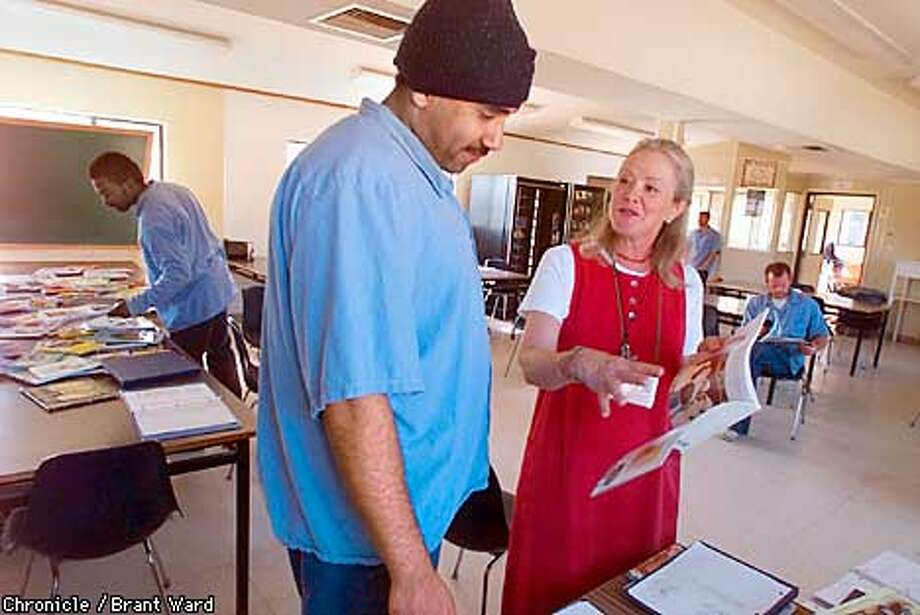 NBQUENTIN3-21MAR01-NF-BW--Deborah Scott, an instructor at San Quentin's family literacy class, shows Anthony Scott one of her favorite books. By Brant Ward/Chronicle Photo: BRANT WARD