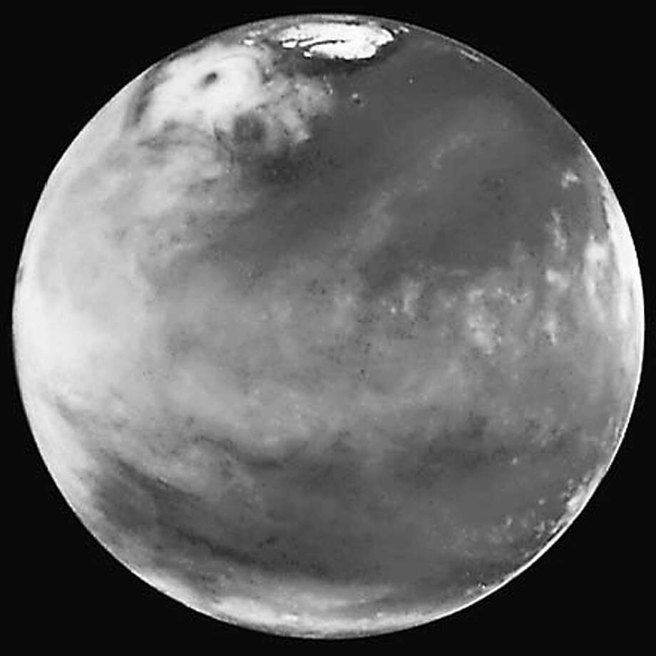 Here is the discovery image of the Martian polar storm as seen in blue light (410 nm). The storm is located near 65 deg. N latitude and 85 deg. W longitude, and is more than 1000 miles (1600 km) across. The residual north polar water ice cap is at the top of the image. A belt of clouds like that seen in previous telescopic observations during this Martian season can also be seen in the planet's equatorial regions and northern mid-latitudes, as well as in the southern polar regions. The volcano Ascraeus Mons can be seen as a dark spot poking above the cloud deck near the western (morning) limb. This extinct volcano towers nearly 16 miles (25 km) above the surrounding plains and is about 250 miles (400 km) across. HANDOUT Photo: HANDOUT