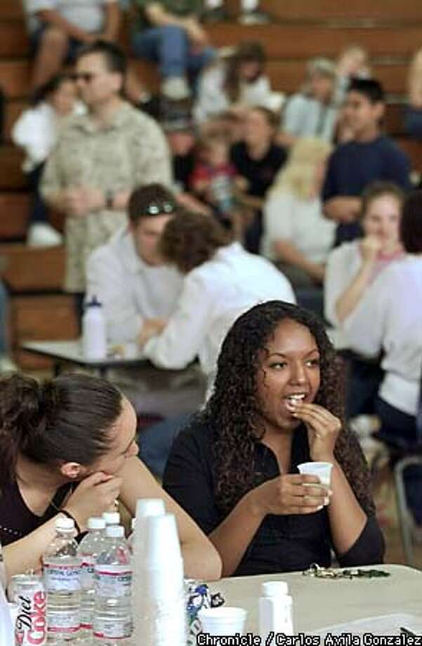 Livermore High student Sojourna Jennings, 17, took an antibiotic in the school gym as classmate Adriana Mendoza, 18, looked on. Chronicle photo by Carlos Avila Gonzalez
