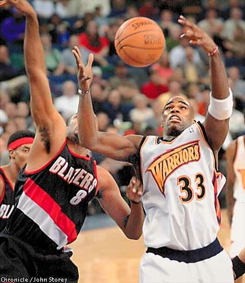 WARRIORS13A-12DEC00-SP-JRS-Antawn Jamison of the Warriors fights with Steve Smith of the Trail Blazers for a rebound in the 1st quarter. The Warriors vs. the Trail Blazers at the Net. Photo by John Storey. Photo: JOHN STOREY