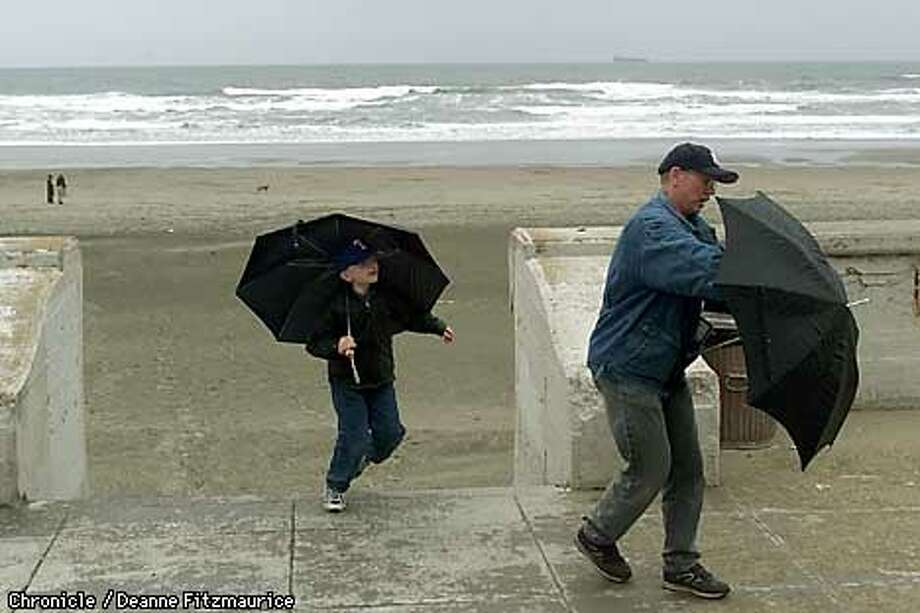 Dennis Hendrickson from Sacramento brings his grandson Celtin Hendrickson to SF for a tour of the city but it started raining when they got to Ocean Beach so they brought out the umbrellas.  CHRONICLE PHOTO BY DEANNE FITZMAURICE Photo: DEANNE FITZMAURICE