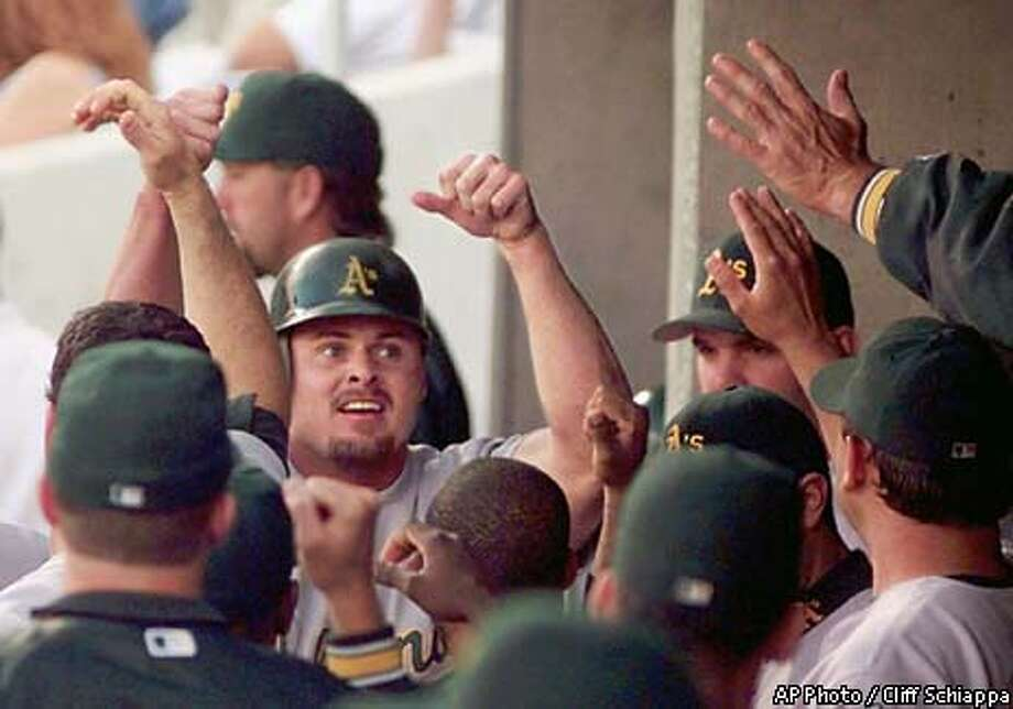 Oakland Athletics' Jason Giambi is congratulated by teammates after scoring from second on a single by John Jaha during the first inning, Tuesday, May 18, 1999, against the Kansas City Royals at Kauffman Stadium in Kansas City, Mo. (AP Photo/Cliff Schiappa) Photo: CLIFF SCHIAPPA