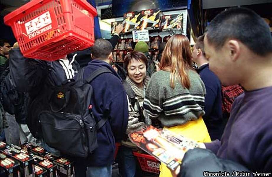 "Shin Hasegawa, center, pushes his way through the crowd to get to his friend Tomo Ichitsubo, right, during FAO Schwarz's sale of the newest ""Star Wars"" toys from the new movie ""The Phantom Menace.""  BY ROBIN WEINER/THE CHRONICLE Photo: ROBIN WEINER"