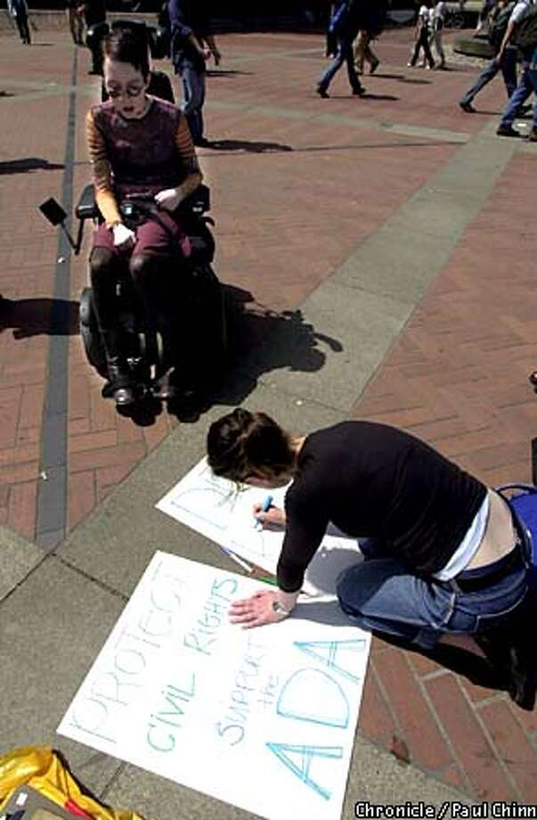 Jessie Alpaugh, an art history major at the University of California at Berkeley, watched as friend Emily Teplin prepared a picket sign before a campus rally yesterday. Chronicle photo by Paul Chinn