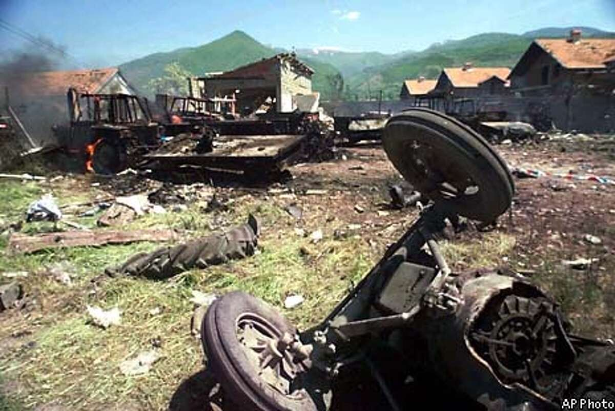 With an overturned tractor seen at right, wreckage continues to burn Friday, May 14, 1999 in Korisa, Kosovo, Yugoslavia, 5 km (3 miles) north of Prizren. According to Yugoslav news reports, 50-100 civilians were killed and dozens seriously injured in an overnight attack on the village attributed to NATO. (AP Photo)