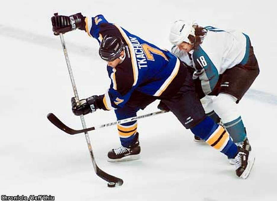 Mike Ricci of the Sharks battles Keith Tkachuk of the St. Louis Blues for the puck in the first period in game 3 of the NHL playoffs at the Compaq Center on Monday night in San Jose. Photo by Jeff Chiu / The Chronicle. Photo: Jeff Chiu