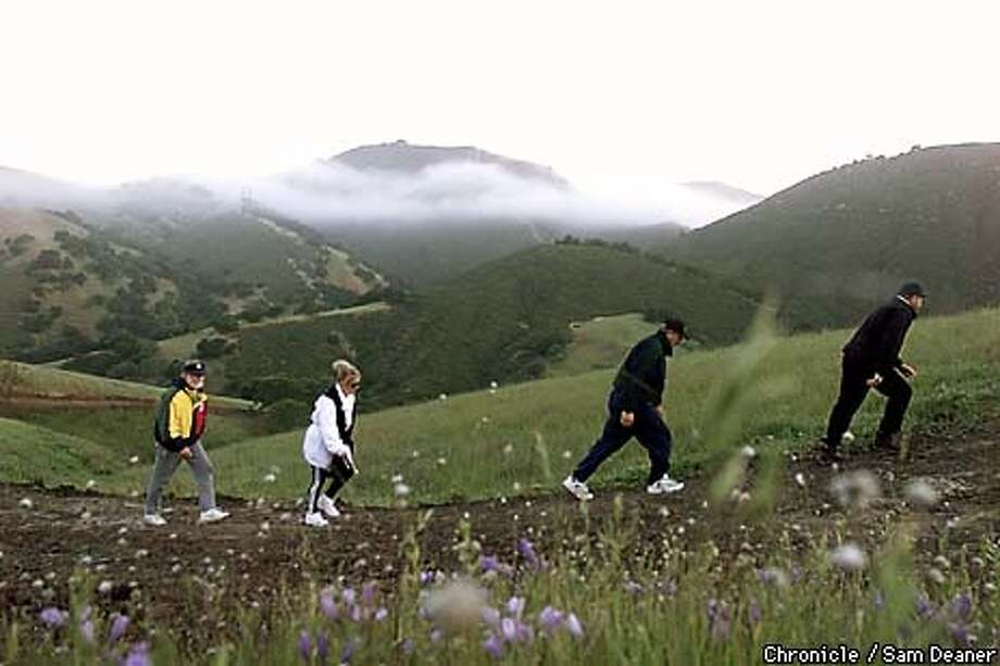Steve Beinke, 48, (from left), Chris Pontious, 47, Don Romero, 51, and Victor VandenBerghe, 51, hike on open space behind Blackhawk as the sun rises Thursday. The land is the last 511acre installment of 2,250 acres donated by Blackhawk to Mount Diablo State Park and there will be a dedication ceremony Saturday. Steve Beinke, the president of Blackhawk, has been hiking these hills with his friends for twelve years. They walk 7-days a week. CHRONICLE PHOTO SAM DEANER Photo: SAM DEANER