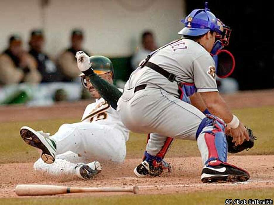 Oakland Athletics' Terrence Long, left, slides into home ahead of the tag by Texas Rangers catcher Ivan Rodriguez to score on a double by Ramon Hernandez in the fourth inning Sunday, April 15, 2001, in Oakland, Calif. (AP Photo/Bob Galbraith) Photo: BOB GALBRAITH