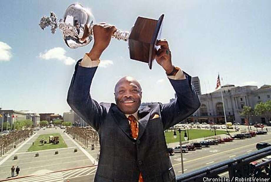 Standing on the balcony of City Hall and the Civic Center in the background, San Francisco Mayor Willie Brown holds up a trophy that either the city of San Francisco or Oakland will win during the Great Sweep IV.  BY ROBIN WEINER/THE CHRONICLE Photo: ROBIN WEINER
