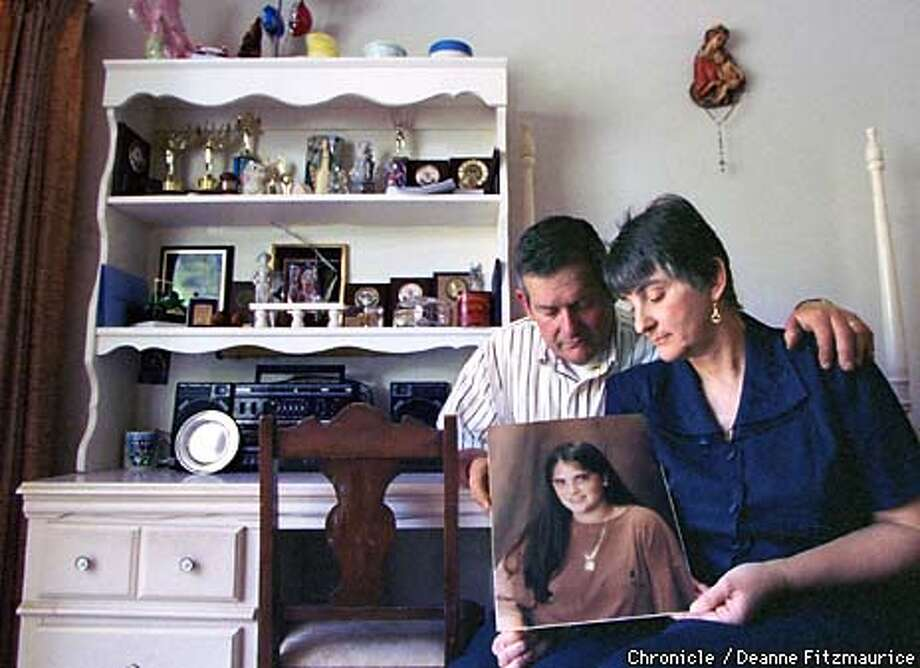 Elmer and Shirley Micheletti hold a picture of their daughter, Michele, 18, who was killed by a car while crossing a street in front of her school dorm at MIT in Cambridge, Massachusetts. The parents are now on a crusade to have a stoplight installed in this potentially dangerous crossing. They are sitting in her bedroom in their Millbrae home with many of her academic awards in her bookshelf. CHRONICLE PHOTO BY DEANNE FITZMAURICE Photo: DEANNE FITZMAURICE