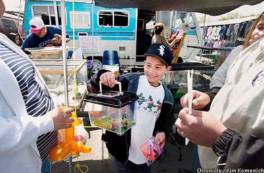 ANIMALS15c-C-14APR01-SZ-KK  A visit to the Berryessa Road Flea Market shows that the San Jose City Council's ban on live animal sales has been interpreted differently by sellers. The dogs and bunnies are gone, but birds and iguanas remain for sale. Gerardo Martinez, 5, of Bay Point checks out his new iguana as his father, Gerardo, Sr. holds the iguana care instructions provided by Rueben and Rebecca Mendoza of R&B Iguana Imports (that's the Mendozas in the background). CHRONICLE PHOTO BY KIM KOMENICH Photo: Kim Komenich