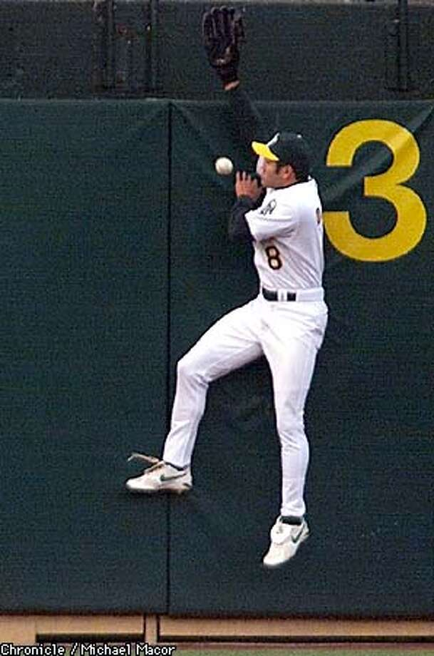 A's outfielder Johnny Damon couldn't handle Rusty Greer's shot to the left-field wall. Chronicle photo by Michael Macor