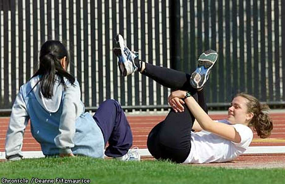 Making Tracks: Maja Ruznic talks with a teammate while she stretches alongside the track during practice at City College of San Francisco. Chronicle photo by Deanne Fitzmaurice