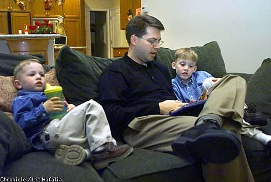 Attorney Craig Menden relaxed with his sons, reading to Connor, 5, while Austin, 3, watched a video. Chronicle photo by Liz Hafalia