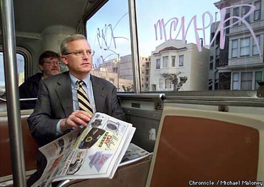 Michael Burns, the new GM of Muni reads the paper next to graffiti painted windows as he commutes to work on the #1 California line bus. Burns does not own a car and relies on muni for his transportation.  BY MICHAEL MALONEY/THE CHRONICLE Photo: MICHAEL MALONEY