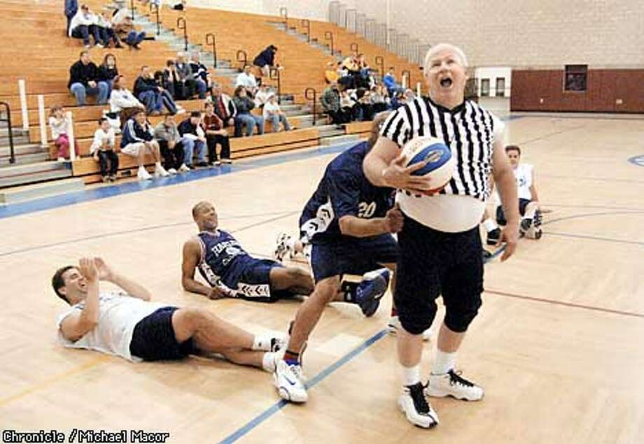 All Dressed Up: Referee Dan Largent's uniform is rearranged by Harlem Clown Bernard James. Chronicle photo by Michael Macor