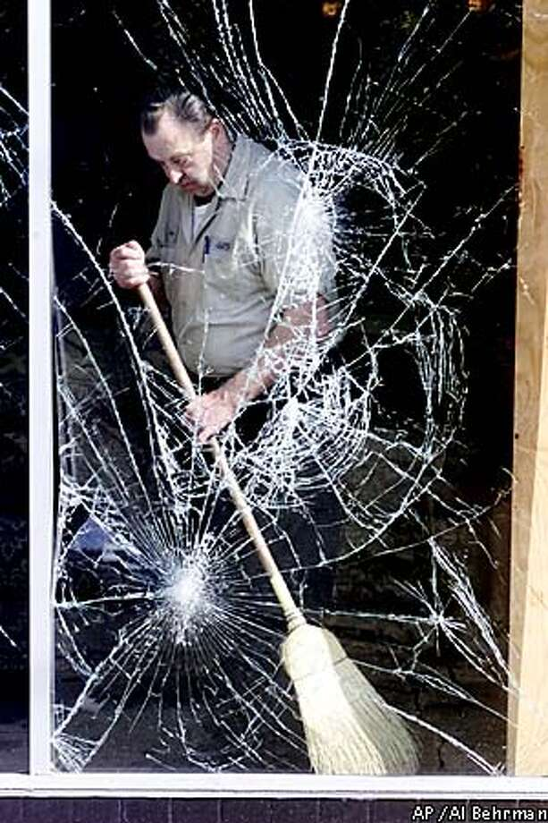Gene Jones swept up glass inside Leader Furniture in the aftermath of riots sparked by the police slaying of an unarmed black man. Associated Press photo by Al Behrman