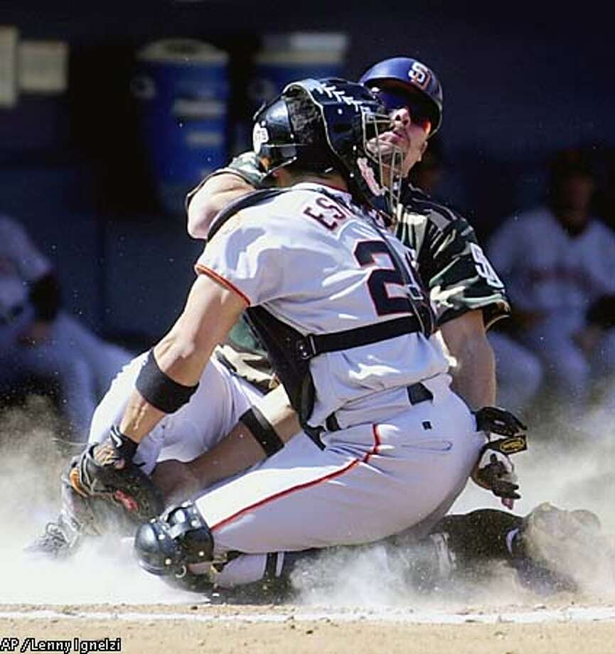 San Diego's Ryan Klesko and Giants catcher Bobby Estalella collide at home plate as Klesko scores from third on a sacrifice fly in the fourth inning. Associated Press photo by Lenny Ignelzi