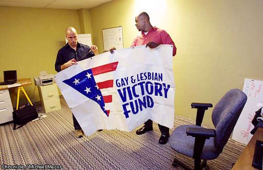 """The """"Gay and Lesbian Victory Fund"""" opened it's doors on Monday. (Director) Tony Esoldo, left and Byron Mills, (Developement Manager Western Office) hang their banner inside the Mission St. office. by Michael Macor/The Chronicle"""