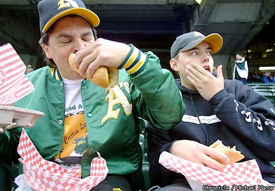 AHHHH!: Rich and Chris Heavingham of Castro Valley dig in before last Friday's opener. Chronicle photo by Michael Macor