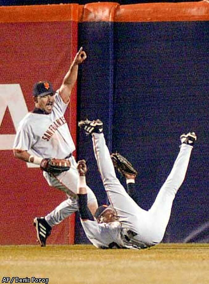 Marvin Benard celebrated as right fielder Eric Davis made a tumbling catch in the fifth inning. Associated Press photo by Denis Poroy