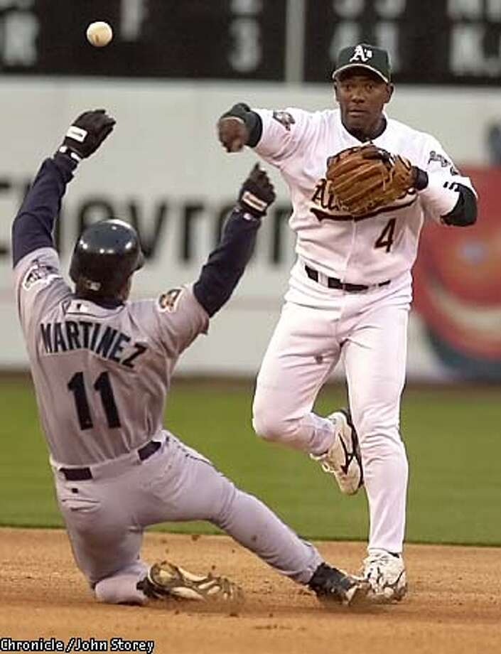 Miguel Tejada throws out the Mariners' Edgar Martinez in a double play in the first inning. Chronicle photo by John Storey