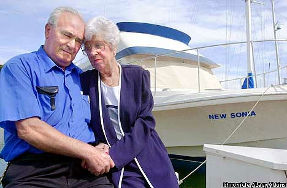 """Left to right--- Bonny and wife Marty Almeida along side of their 45 foot Chris Craft at the San Francisco Yatch Harbor, Sunday April 9,01. They loaned their boat """"New Sonia"""", to a man who after 8 months left it """"trashed"""". Photo By Lacy Atkins/San Francisco Chronicle"""