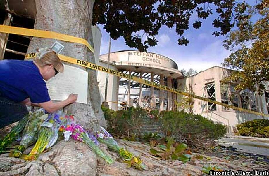 "Vallejho resident Laura Brackett writes ""thoughts and prayers"" on a sign with flowers nearby, as residents start a memorial next to the front of the fire damaged Steffan Manor school in Vallejo. No injuries were reported at the scene of the fire. Chronicle Photo by Darryl Bush Photo: Darryl Bush"