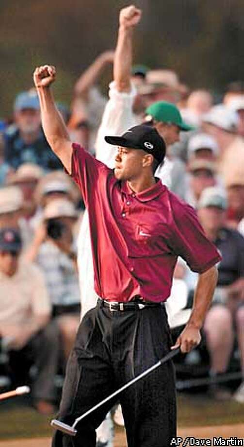 Tiger Woods reacts on the 18th hole after winning the 2001 at the Augusta National Golf Club in Augusta, Ga., Sunday, April 8, 2001. Woods captured this second title, defeating David Duval by two strokes. (AP Photo/Dave Martin) Photo: DAVE MARTIN