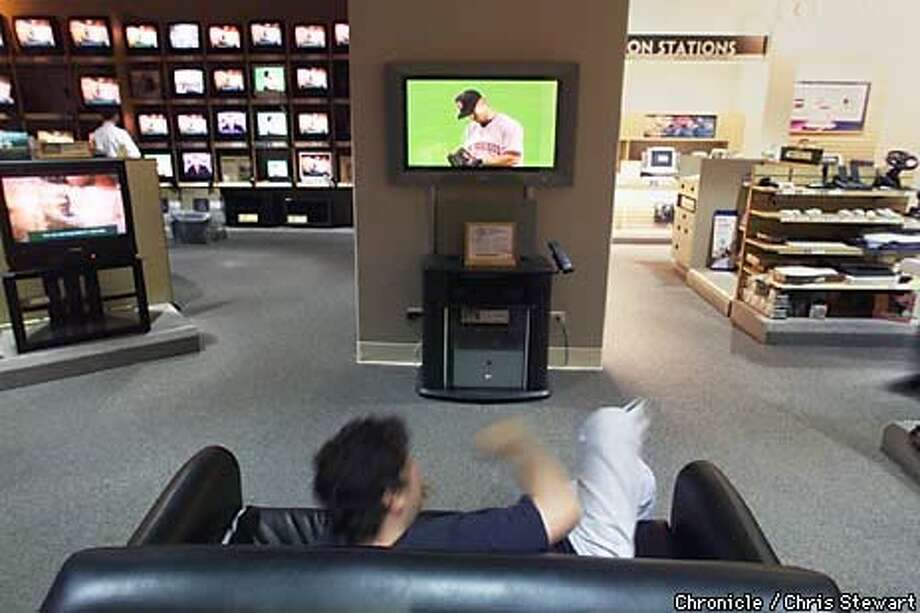 A customer at the Good Guys store in the Stonestown Galleria in San Francisco watched the Giants on a big-screen TV. Chronicle Photo by Chris Stewart