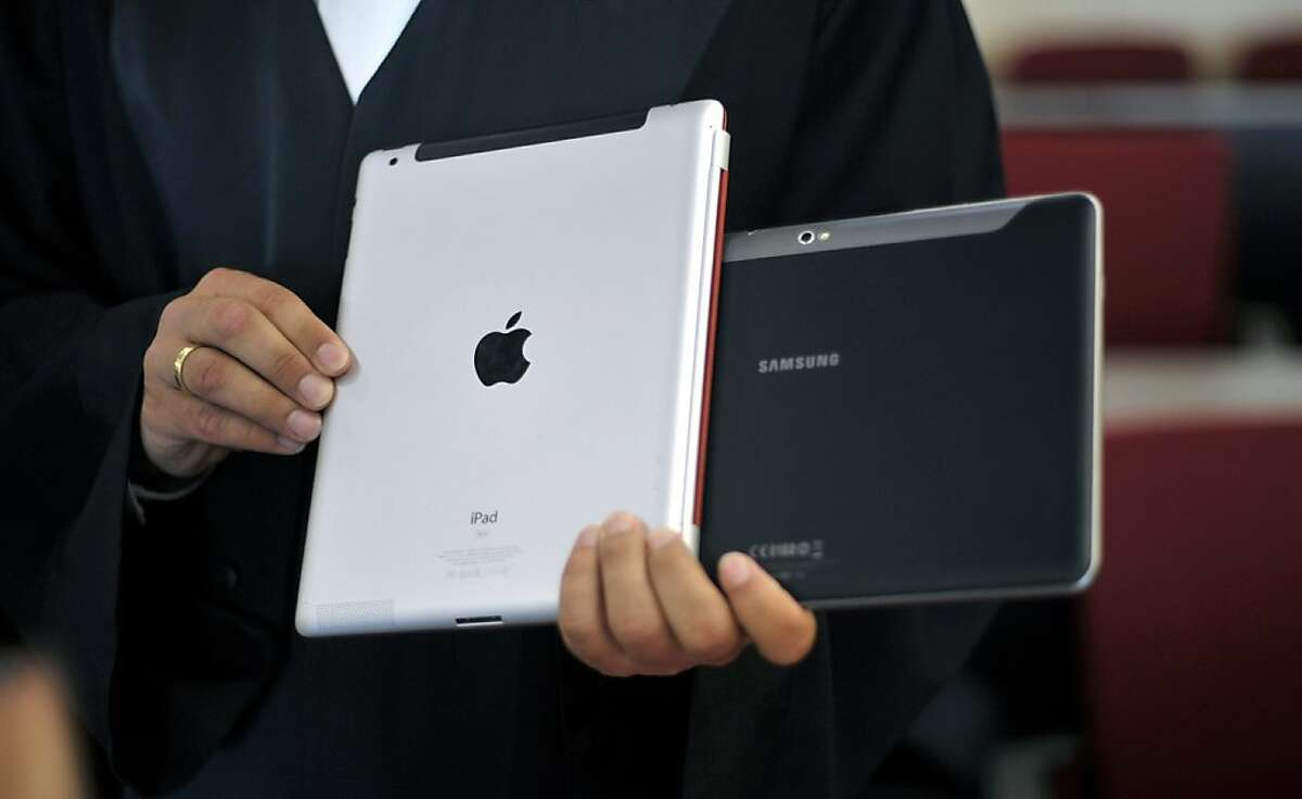 FILE - In this Aug. 25, 2011 file photo a lawyer holds an Apple iPad and a Samsung Tablet-PC at a court in Duesseldorf, Germany. The Duesseldorf state court ruled Tuesday, Jan. 31, 2012, that neither the South Korean company's Galaxy Tab 10.1 nor the Galaxy Tab 8.9 could be sold in Germany because they were in violation of unfair competition laws. A German appeals court has upheld a decision prohibiting Samsung Electronics Co. from selling two of its tablet computers in Germany, agreeing with Apple Inc. that they too closely resemble the iPad2. (AP Photo/dapd, Sascha Schuermann, file)