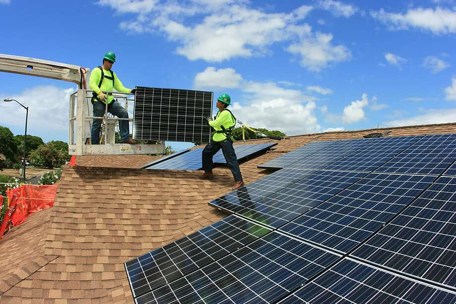 SolarCity workers install panels on military housing at Joint Base Pearl Harbor-Hickam in Hawaii. San Mateo's SolarCity and other installers are booming as customers take advantage of falling panel prices. Photo: SolarCity