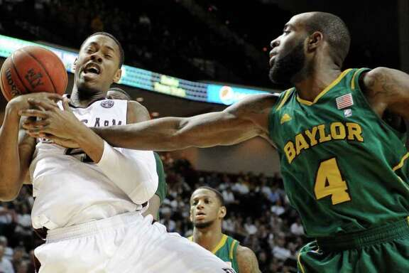 Baylor forward Quincy Acy (4) knocks the ball away from Texas A&M center Keith Davis, left, in the first half of an NCAA college basketball game on Wednesday, Feb. 1, 2012, in College Station, Texas. (AP Photo/Pat Sullivan)